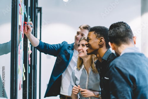 Fototapety, obrazy: Cheerful black man looking at glass wall with colleagues