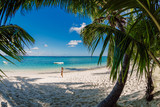 Young woman in bikini relax at tropical palm beach. Tropical vacation