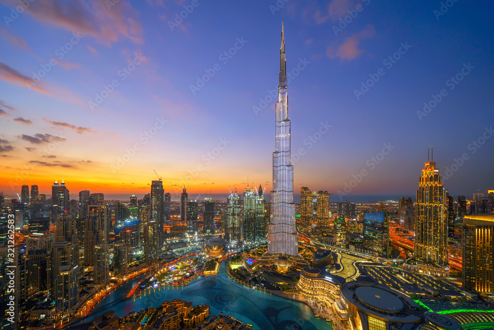 Fototapeta Aerial view of Burj Khalifa in Dubai Downtown skyline and fountain, United Arab Emirates or UAE. Financial district and business area in smart urban city. Skyscraper and high-rise buildings at night.