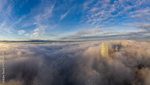 Photo Sea of fog over the Basel city, Switzerland at sunrise shot from a drone