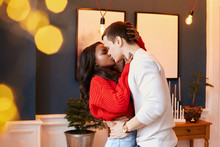 Interracial Married Couple Kissing On Valentine's Day Holiday. A Guy Hugs A Black Girl At The Waist. Happy Relationship.