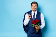 Happy Guy With Red Flowers Isolated Over Blue Background. Bearded Male Hold Blazer On Back, Look At Camera And Smile. Man Came On A Date With Bouquet Of Flowers. Dating, Celebration, Love, Holidays