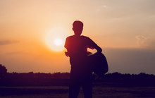 The Silhouette Of A Guitarist Who Holds A Guitar And Has A Sunset, Silhouette Concept.