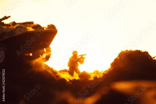 Fototapeta Battle scene with toy soldier near tank on battleground on yellow background obraz