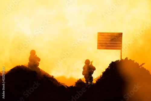 Fototapeta Battle scene with toy soldiers near american flag with fire at background obraz
