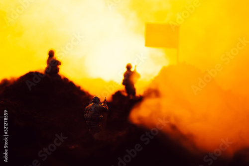 Fototapeta Selective focus of toy warriors on battleground with smoke, flag and fire at background obraz