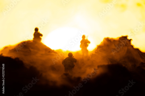 Fototapeta Selective focus of toy warriors on battleground with sunset at background, battle scene obraz