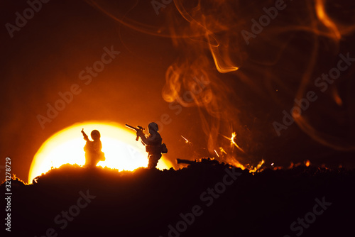 Fototapeta Battle scene with toy soldiers on battleground with smoke and sunset at background obraz