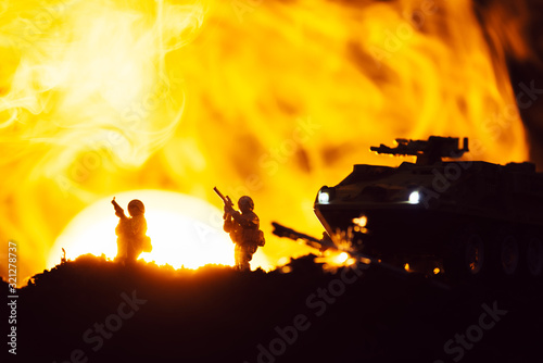 Fototapeta Scene of battle with toy warriors, tank and smoke with sunset at background obraz