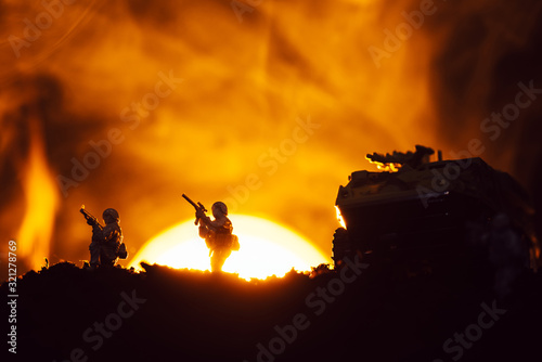 Fototapeta Silhouettes of toy warriors and tank on battleground with sunset and fire at background obraz