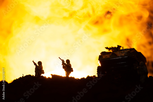 Fototapeta Battle scene with silhouettes of toy tank and soldiers with fire at background obraz