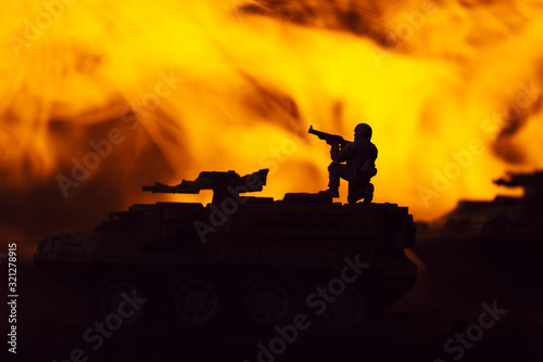Fototapeta Battle scene with silhouettes of toy warrior and tanks with fire at background obraz