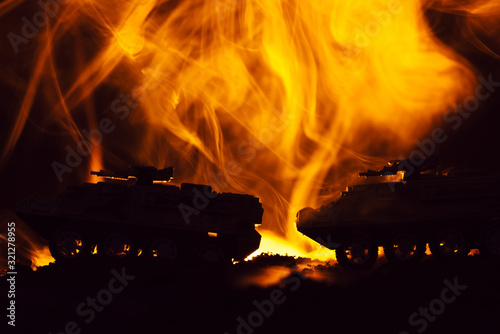 Fototapeta Battle scene with toy tanks and fire on black background obraz