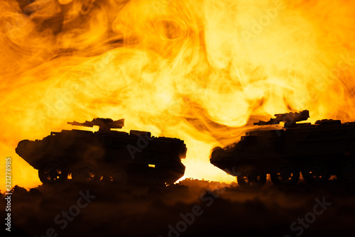 Fototapeta Battle scene with toy tanks and fire at background obraz