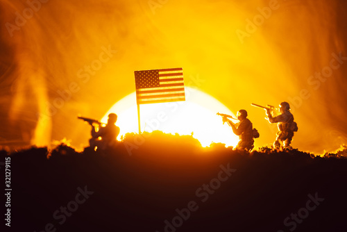 Fototapeta Battle scene with toy warriors near american flag in smoke with sunset at background obraz