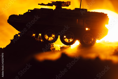 Fototapeta Battle scene with toy tank in fire and sunset at background obraz
