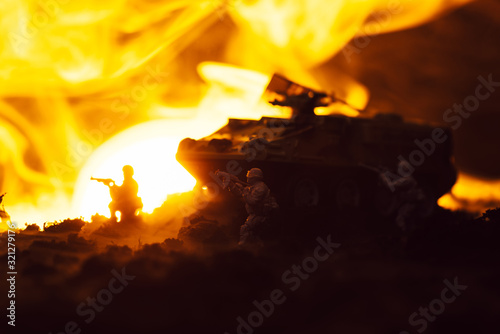 Fototapeta Toy soldiers with tank, fire and sunset on black background, battle scene obraz