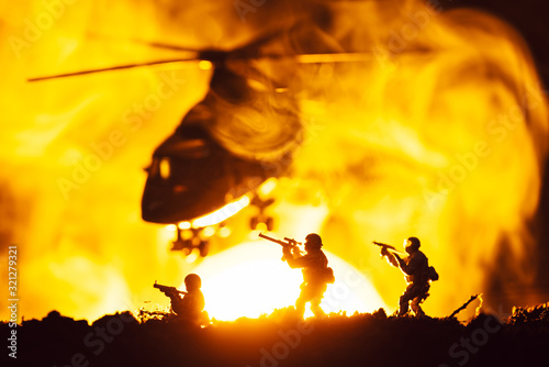 Fototapeta Battle scene with toy warriors and helicopter in smoke with sunset at background obraz