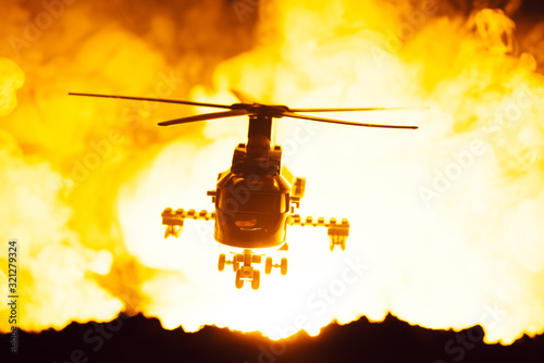 Fototapeta Battle scene with toy helicopter and fire at background obraz