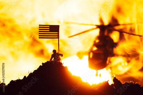 Fototapeta Battle scene with toy warrior near american flag and helicopter in fire with sunset at background obraz