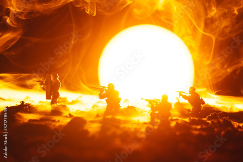 Fototapeta Battle scene of toy soldiers in smoke with sunset at background obraz