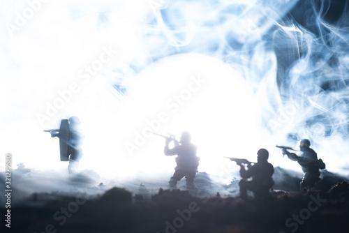Fototapeta Battle scene with toy soldiers in smoke on black background obraz