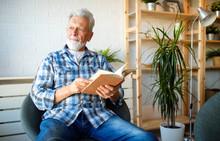 Senior Man At Home Reading Book And Enjoying Retirement, Penison