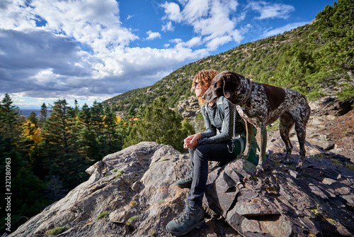 Photo a young woman and her dog hiking to the top of a mountain