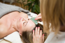 Woman Having An Gua Sha Facial...