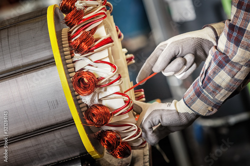 Fototapeta Skilled industrial worker assembling a large electric motor