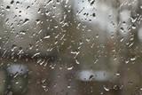 Fototapeta Fototapety do łazienki - Krople deszczu na szybie, w tle nieostry zarys domu.