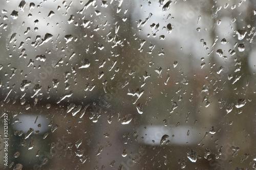 Krople deszczu na szybie, w tle nieostry zarys domu.