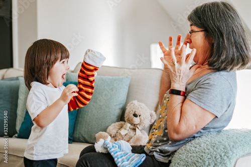 Cute little cheerful child playing with his older granmother with bright hand toy at home Canvas Print