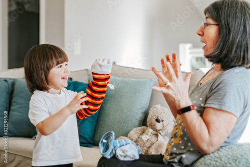 Photo Cute little cheerful child playing with his granmother with bright hand-toy at home