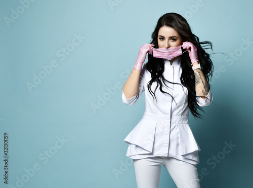 Young brunette woman doctor, nurse, cosmetologist, chemist in stylish uniform is Tablou Canvas