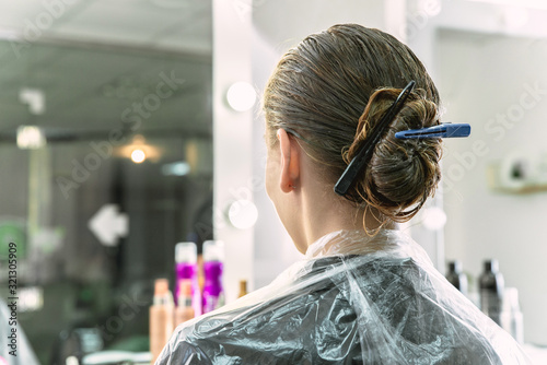 hair coloring in a beauty salon, young girl during dyeing process