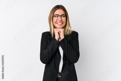 Young business caucasian woman keeps hands under chin, is looking happily aside Canvas Print