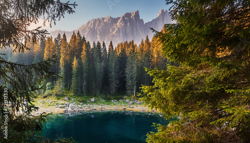 Wall mural - Incredible nature landscape.Sunny autumn day in Dolomites Alps. Lake Carezza with Mount Latemar, Bolzano province, South tyrol, Italy. popular travel locations. Picture of wild area