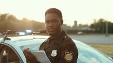 Serious Black Policeman Writin...