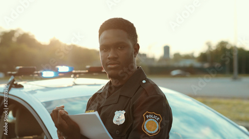 Fotografia, Obraz Serious black policeman writing notes working outdoors leaning on the police car hood posing at sunlight looking on camera in the city street