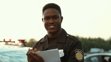Portrait Of Cheerful Smiling Policeman Holding Papers Leaning On The Police Car Posing At Sunlight. Happy American Cop Enjoying His Work Outdoors.