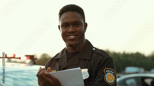 Fototapeta Portrait of cheerful smiling policeman holding papers leaning on the police car posing at sunlight