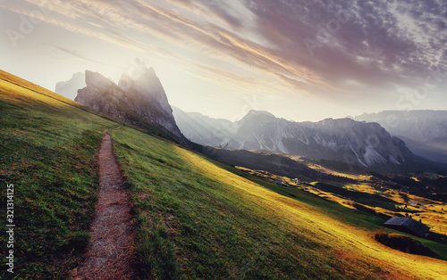 Wall mural - Beautiful alpine highlands with dramatic sky. Incredible view in Dolomite Alps. Awesome nature Landscape. View from Seceda peak on Famous Odle peaks under sunlight during sunrise. Bolzano, Italy,