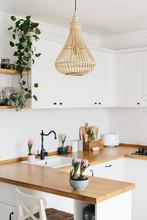 Modern White U-shaped Kitchen In Scandinavian Style. Spring Decoration Spring Flowers