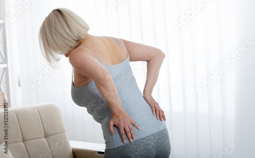 Middle aged woman with pain in the backache and lower back Wallpaper Mural