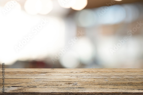 Empty wooden table for present product on coffee shop blur background.