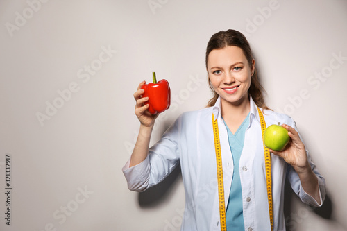 Fototapeta Nutritionist with bell pepper and apple on light grey background. Space for text obraz