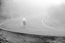Woman Walking On Road In The Fog