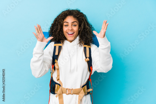 Young african american backpacker woman receiving a pleasant surprise, excited and raising hands Canvas Print