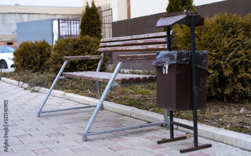 Photo Bench and trash can on the sidewalk
